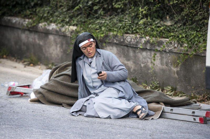 義大利中部24日發生芮氏規模6.2大地震,災情慘重,一位受傷修女癱坐地上傳簡訊,成為這場震災最讓人難忘的畫面之一(AP)
