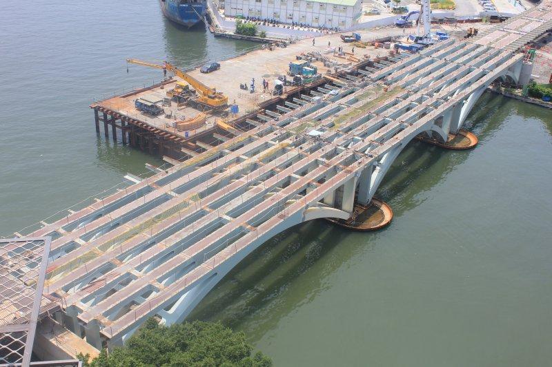串聯愛河兩岸捷運輕軌愛河主橋最後一跨鋼樑,於24日吊裝合攏,整體橋梁主結構中於連通,預訂11月初交付鋪軌。(高市捷運局提供)