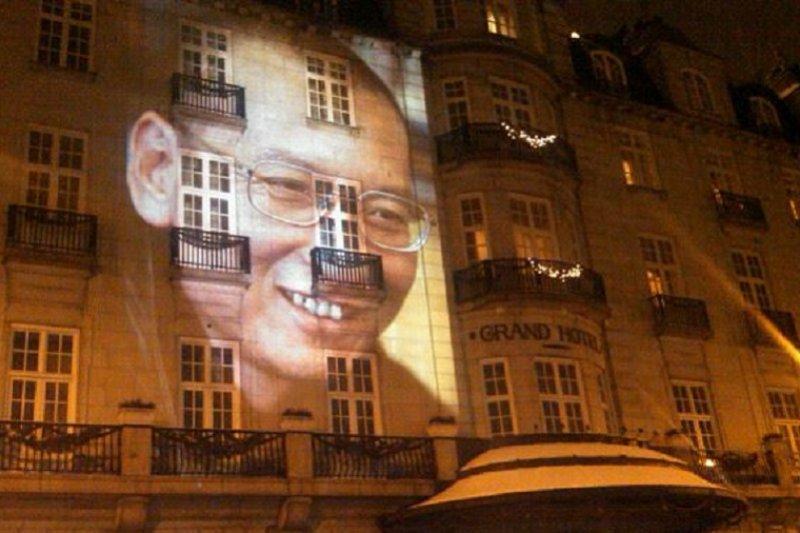 圖為劉曉波的巨幅頭像投映在奧斯陸大酒店的正門外牆。(美國之音王南攝/維基百科)