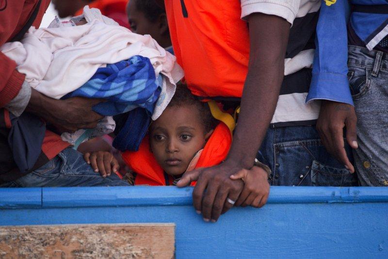 義大利海巡隊與非政府組織合作,29日在利比亞西部港口薩卜拉塔以北的海域,營救3千名難民,這位難民小男孩擠在載了700人的小木船上,等待救援。(美聯社)