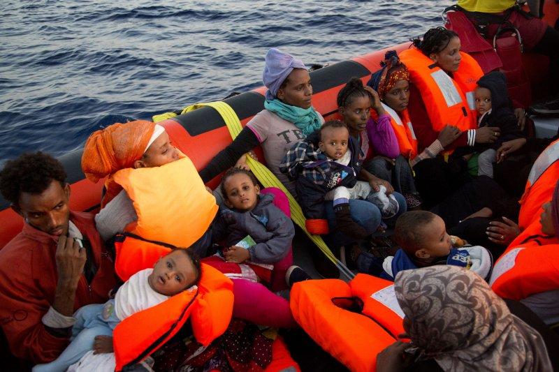 義大利海巡隊與非政府組織合作,29日在利比亞西部港口薩卜拉塔以北的海域,營救3千名難民。這些難民登上救援船後,茫然地抱著自己的孩子。(美聯社)
