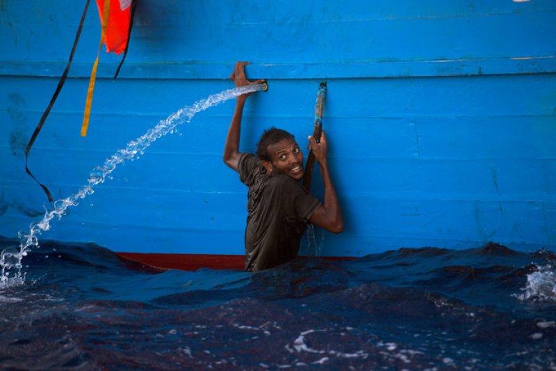 義大利海巡隊與非政府組織合作,29日在利比亞西部港口薩卜拉塔以北的海域,營救3千名難民,一名男性攀著船隻,等待救援。(美聯社)
