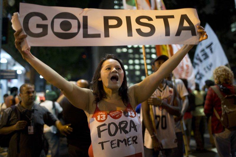 里約熱內盧一名婦女要代理總統特梅爾滾蛋,高舉「政變領袖」的標語。(美聯社)
