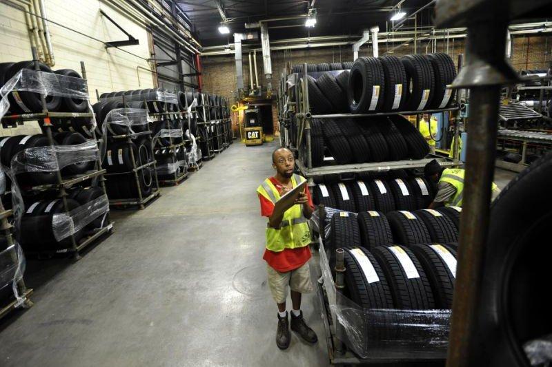 美國一位汽車維修廠的員工正在清點輪胎。(美聯社)