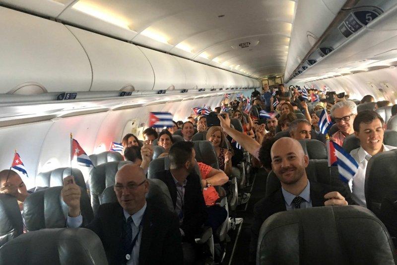 半世紀來首架由美國直飛古巴的定期航班捷藍航空(JetBlue)387客機乘客,在飛機落地前興奮揮舞古巴國旗。(美聯社)