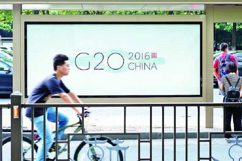 杭州市民行經杭州公車站的G20漼會廣告。(新華社)
