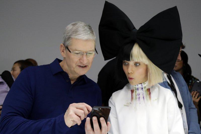 蘋果執行長庫克與模特兒一同把玩iPhone7(美聯社)