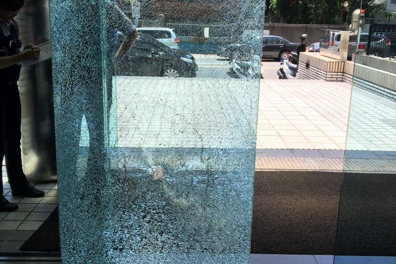 2名騎腳踏車的中年男子朝不當黨產委員會門口丟擲石塊,大門玻璃碎裂。(不當黨產委員會提供)