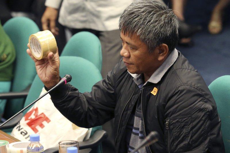 菲律賓前殺手馬托巴托(Edgar Matobato)展示用來捆綁屍體的膠帶。(美聯社)