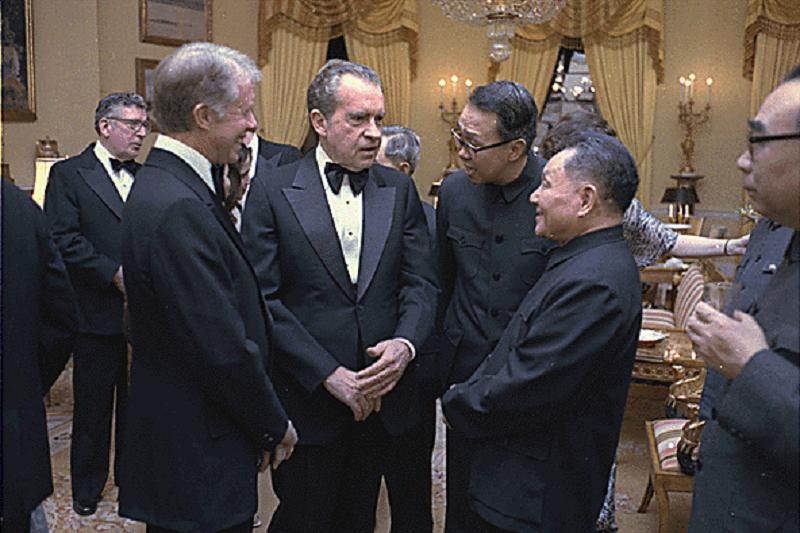 1979年,尼克森在白宮與中華人民共和國國務院副總理鄧小平交談,一旁的是總統吉米·卡特。(維基百科)