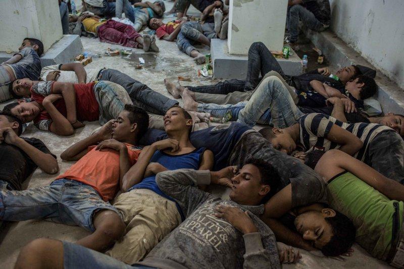 一艘由埃及(Egypt)港口城市羅塞塔(Rosetta)出發的人口走私難民船,於21日翻覆,被救起的倖存者遭警方拘留,大難不死後隨意躺在警局地上睡覺(AP)