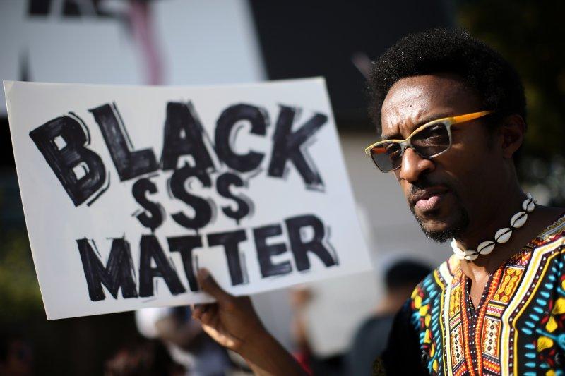 抗議警方濫殺黑人的民眾高舉標語。(美聯社)