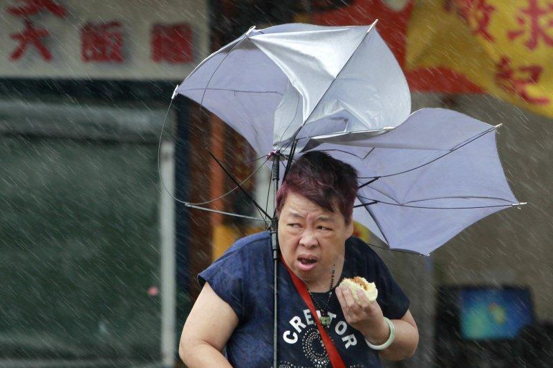 中度颱風橫掃台灣,台北市一位民眾無懼強風讓雨傘開花,在風雨中大啖肉包,登上華爾街日報。(AP)