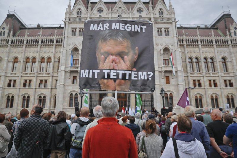 匈牙利總理奧爾班(Viktor Orban)出現在抗議民眾高舉的海報上,上頭用匈牙利文寫著「我又做了什麼?」。(美聯社)