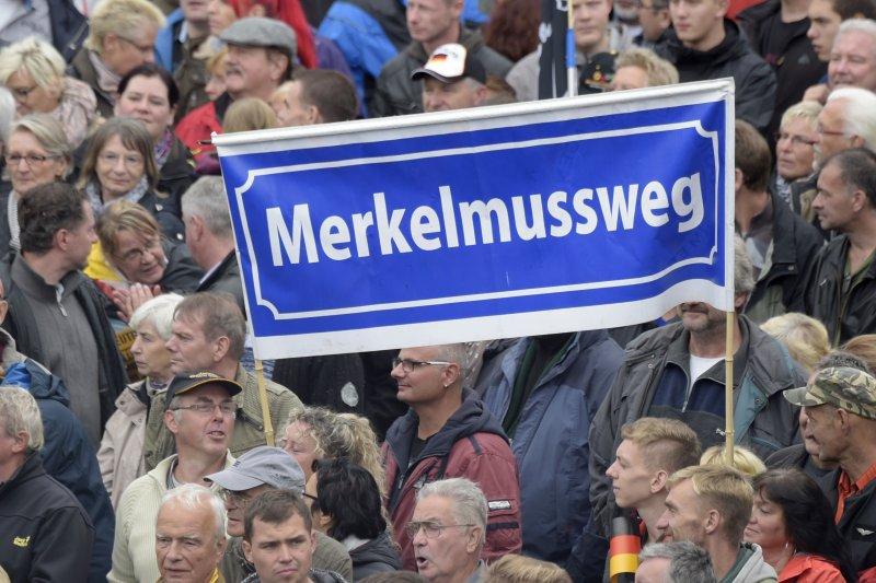 德國民眾在德勒斯登高舉「梅克爾必須滾」(MERKEL MUSS WEG)的旗幟。(美聯社)