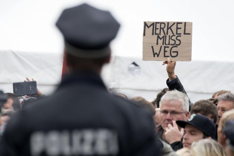 不滿梅克爾難民政策的德國民眾,在德勒斯登要梅克爾滾蛋。(美聯社)