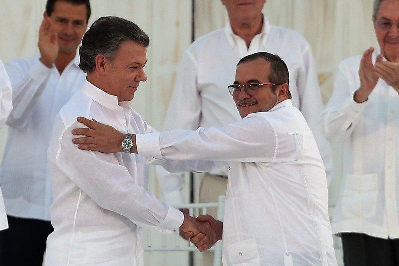 哥倫比亞總統桑托斯(左)和FARC領袖西梅內斯(右)在哈瓦那簽署停火協議。(美聯社)