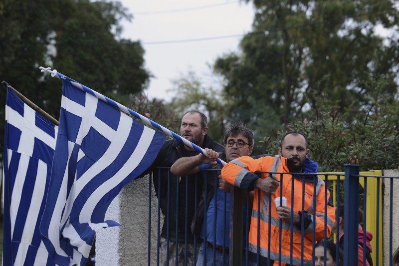 希臘家長在學校外揮舞希臘國旗抗議。(美聯社)
