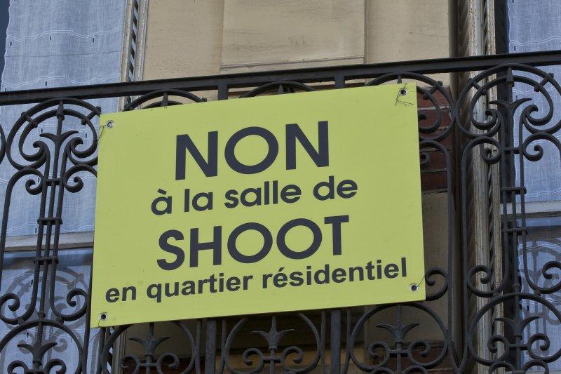 法國第一個合法吸毒室附近的居民在陽台掛出抗議標語,要求「不要在住宅區設立毒品注射室」。(美聯社)