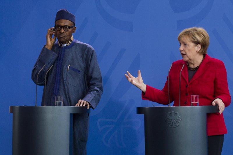 奈及利亞總統布哈里(左)在德國總理梅克爾(右)面前貶低妻子。(美聯社)