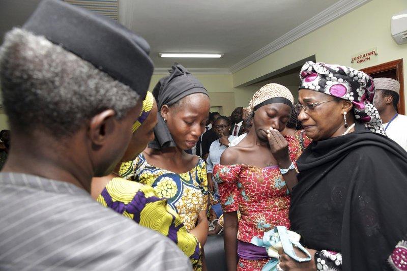 奈及利亞副總統耶米·奧辛巴喬(左)13日探視獲釋的「奇波克女孩」。(美聯社)