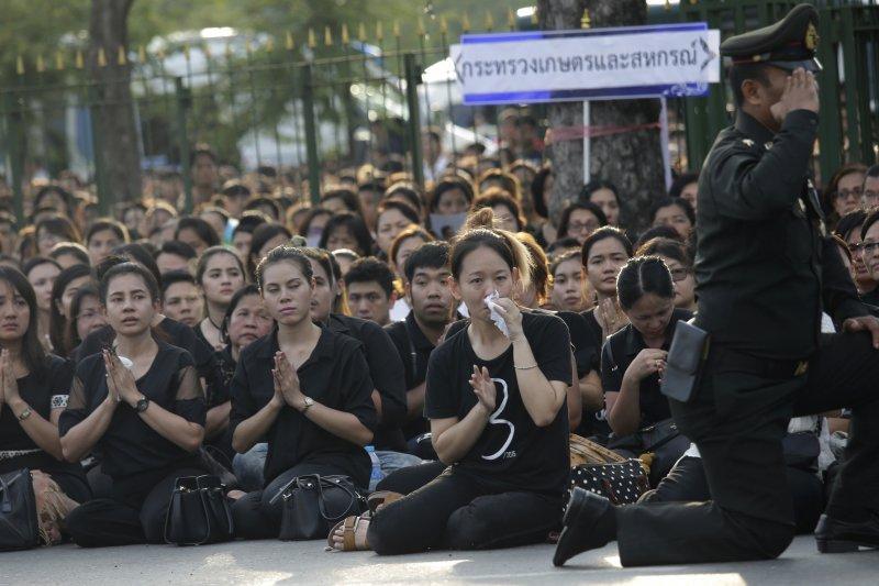 泰國民眾14日在街頭為駕崩泰王蒲美蓬默禱致哀。(美聯社)