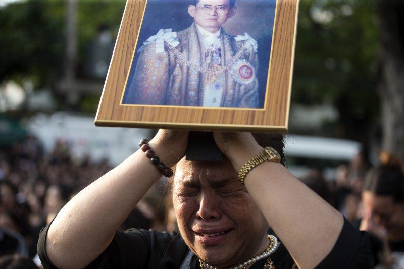 一位泰國婦女14日拿著駕崩泰王蒲美蓬的遺照默禱,等待運送泰王遺體的車隊經過。(美聯社)