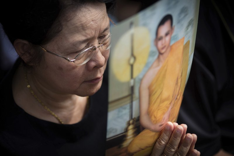 一位泰國婦女15日拿著駕崩泰王蒲美蓬的遺照為他助念默禱。(美聯社)