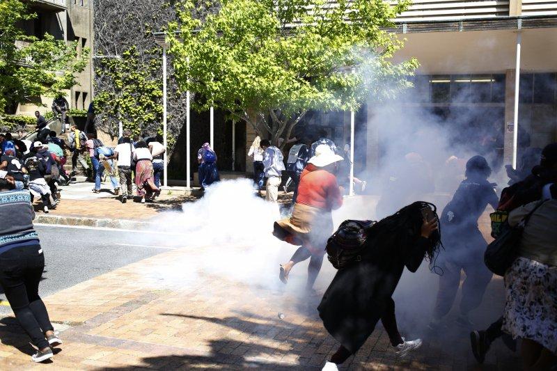南非警方對抗議高學費的大學生施放煙霧彈。(美聯社)
