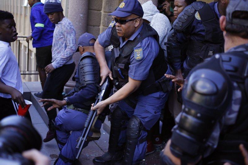南非警方17日在示威大學生打破玻璃後,開始強力驅散。(美聯社)