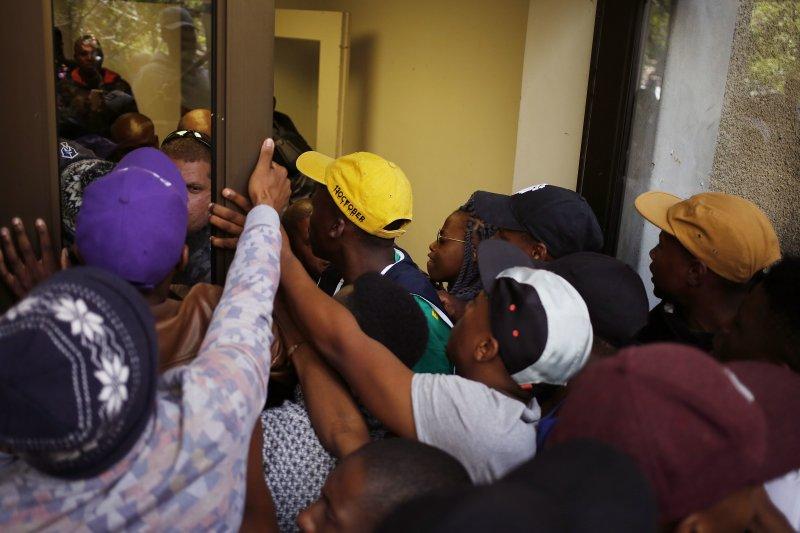 南非開普敦大學的學生17日在學校與校方警衛拉扯,試圖強行進入辦公大樓示威。(美聯社)
