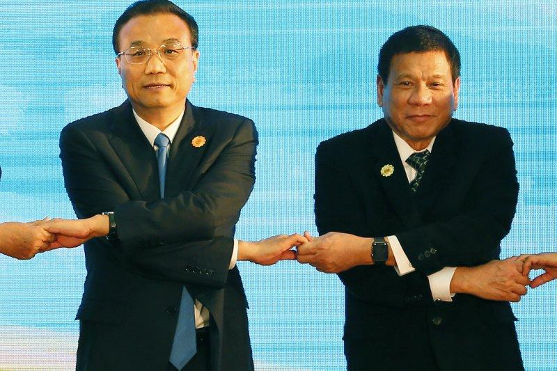 東協會議上,菲律賓總統杜特蒂(右)與中國國務院總理李克強手牽手。(美聯社)
