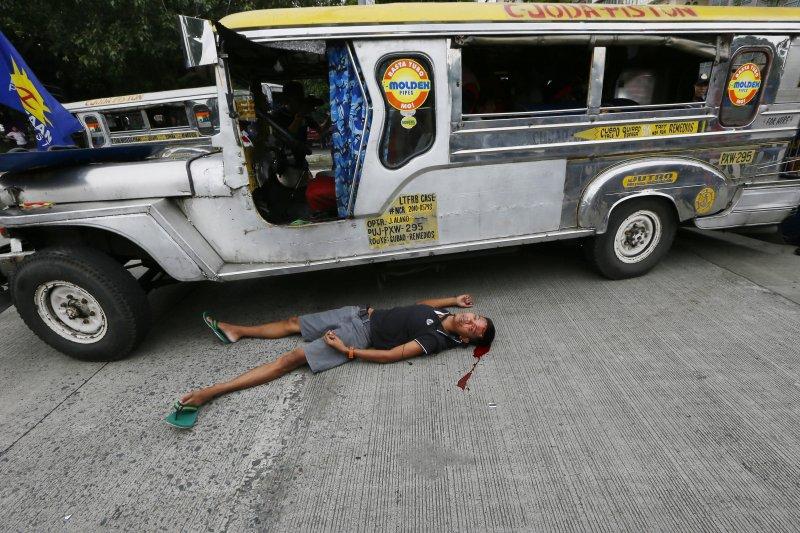 馬尼拉的美國大使館外19日發生嚴重的警民衝突,一位年輕男性滿頭是血、倒在一輛公車旁。(美聯社)