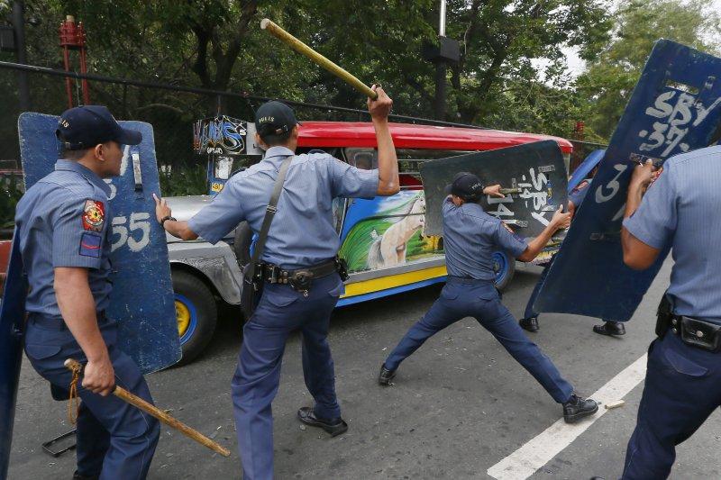 菲律賓警方在19日的警民衝突中壓制抗議者。(美聯社)
