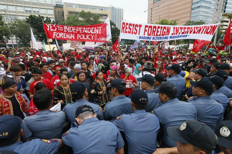 菲律賓民眾19日在馬尼拉的美國大使館附近與警方對峙,抗議標語上寫著「支持總統的外交政策」、「抵抗外國干預」。(美聯社)