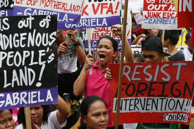 菲律賓民眾19日在馬尼拉的美國大使館附近與警方對峙,抗議標語上寫著「美軍滾出去」、「抵抗外國干預」。(美聯社)