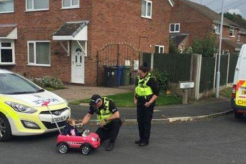 英國警察逗小孩,假裝給開玩具車的兒童進行「酒測」。(BBC中文網)