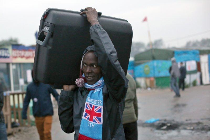 一位寄居在加萊難民營的難民,24日帶著自己的全部家當準備撤離。(美聯社)