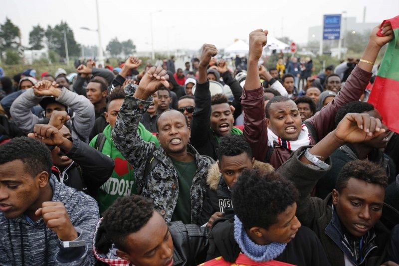 在排隊接受登記的長龍,許多久住加萊的難民們揮臂表示不滿。(美聯社)