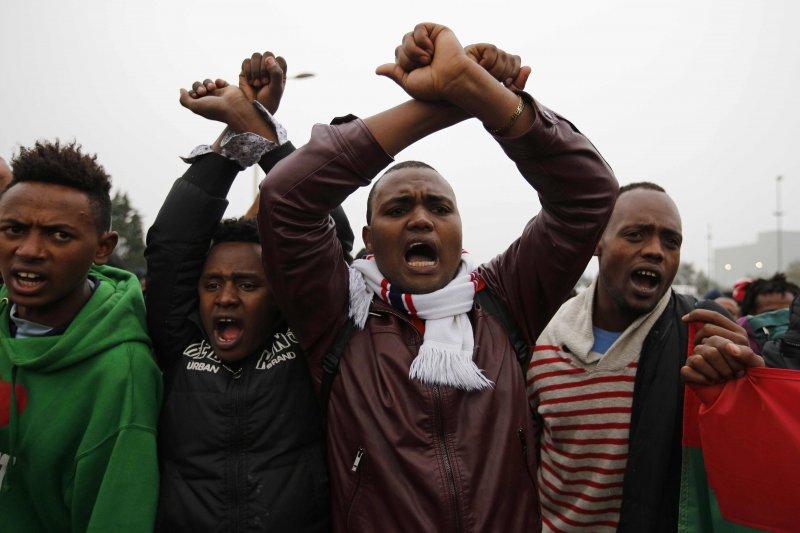準備離開加萊的難民們,在排隊接受登記的長龍中紛紛高舉雙手交叉、表示抗議。(美聯社)