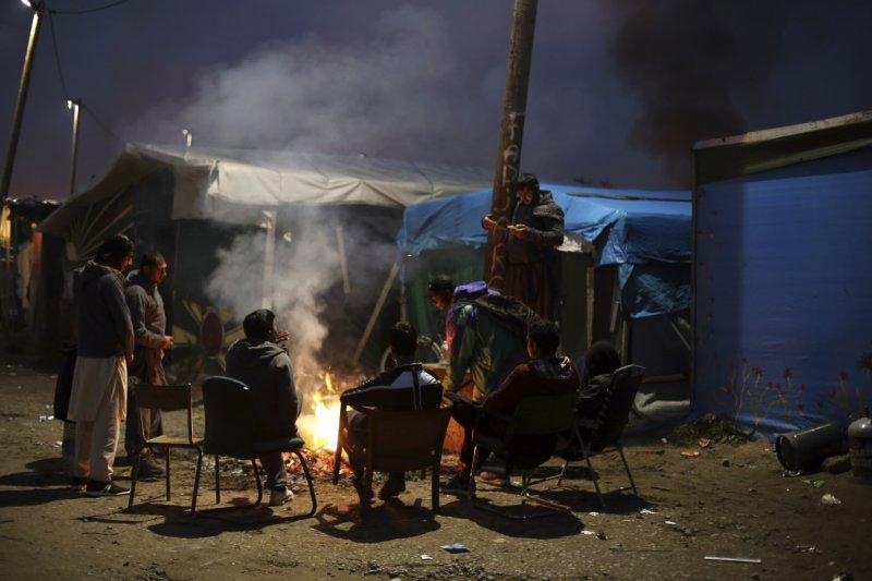 「叢林難民營」的難民們烤火取暖,這也是他們在加萊的最後一夜。(美聯社)