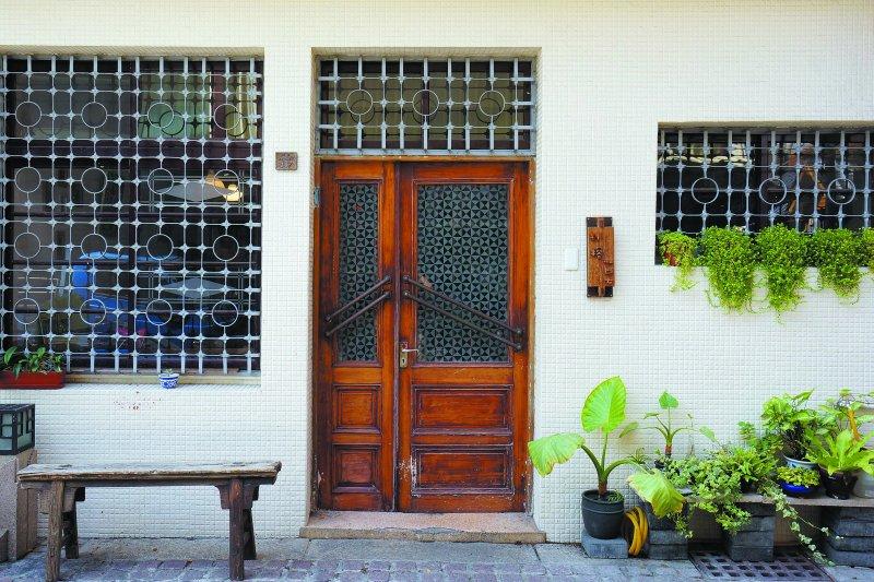 一樓的鐵窗看來像是棋盤上的棋子,裝有舊式銅製門把的門板則去除油漆 露出木門原有色澤。(圖/作者提供)