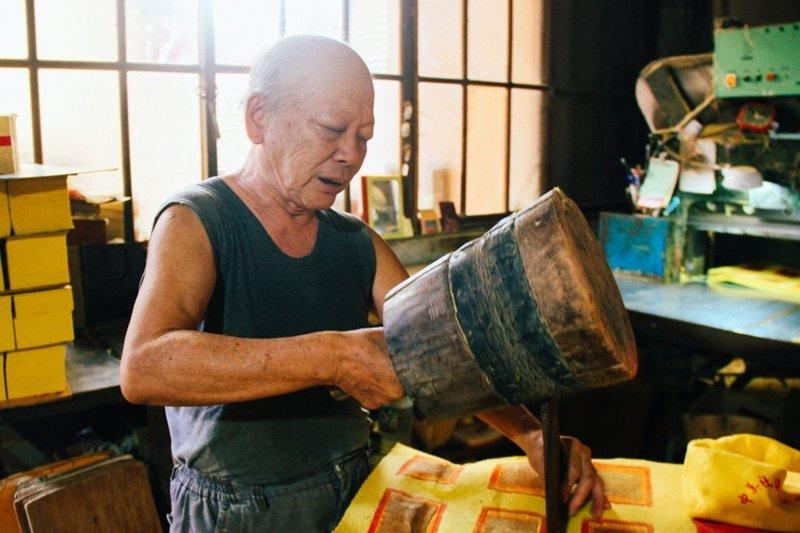 陳坤輝拿著重達十二磅重的木槌,敲在鐵製的刀片上,他說在沒有機器可以裁紙之前,這是將大張紙材成小塊的方法。(圖/文化銀行提供)