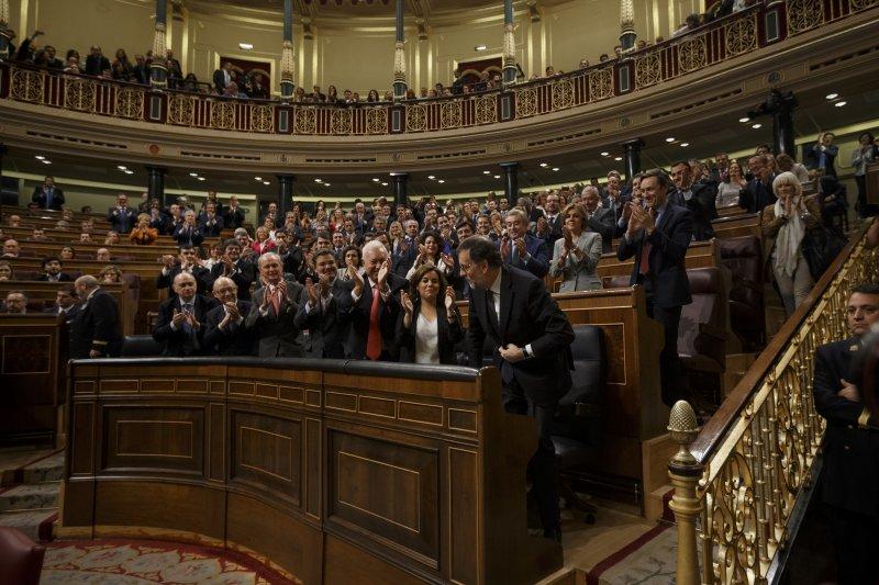 西班牙國會議員起立鼓掌,恭賀拉霍伊內閣通過不信任投票的考驗。(美聯社)