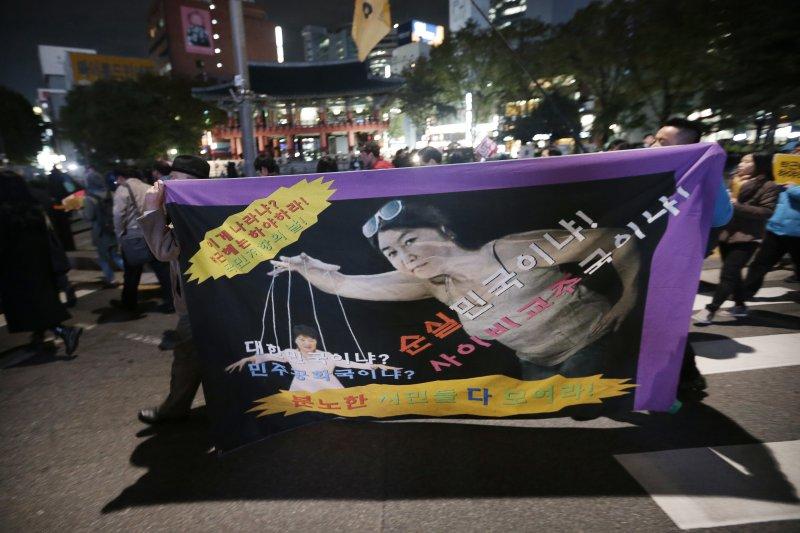 南韓民眾將朴槿惠描繪成遭到崔順實操弄的傀儡。(美聯社)