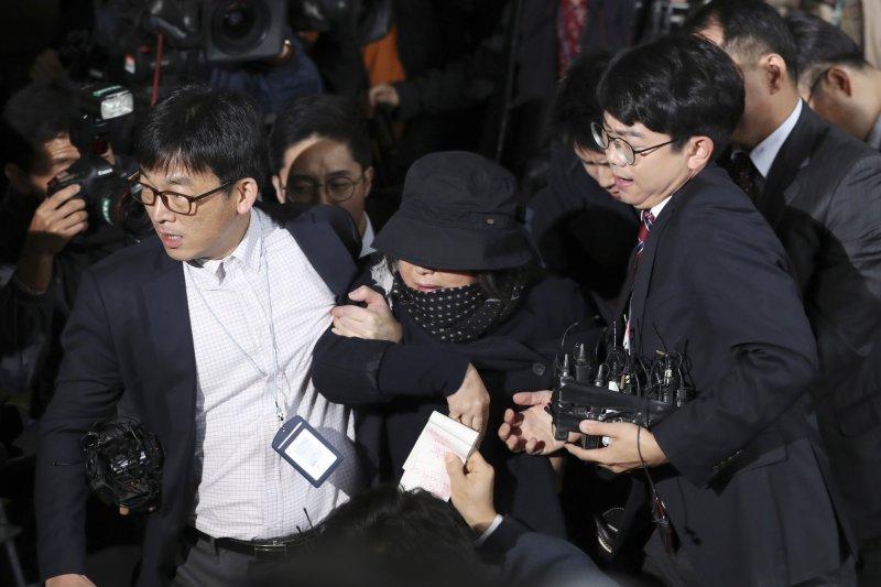崔順實31日在首爾中央地方檢察廳公開現身時的狼狽模樣。(美聯社)