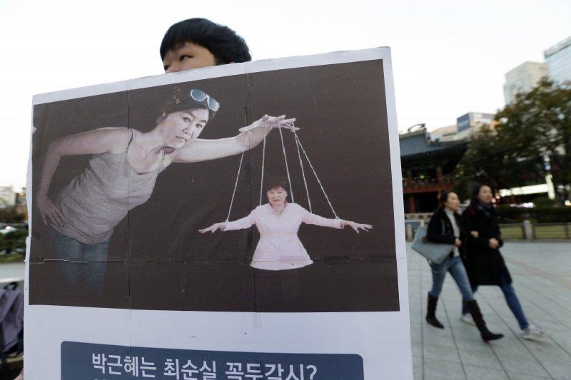 抗議民眾諷刺朴槿惠被崔順實操控。(美聯社)