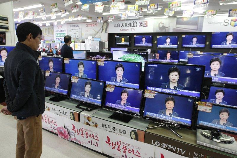 南韓民眾在大賣場觀看朴槿惠道歉。(美聯社)