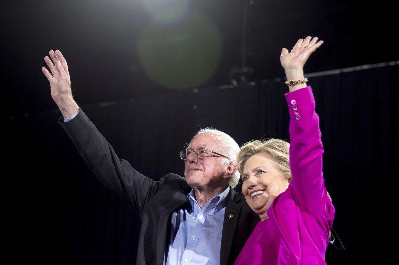 民主黨總統候選人希拉蕊(右)為了拉攏初選對手桑德斯(左)的支持者選票而調整免學貸政策(美聯社)