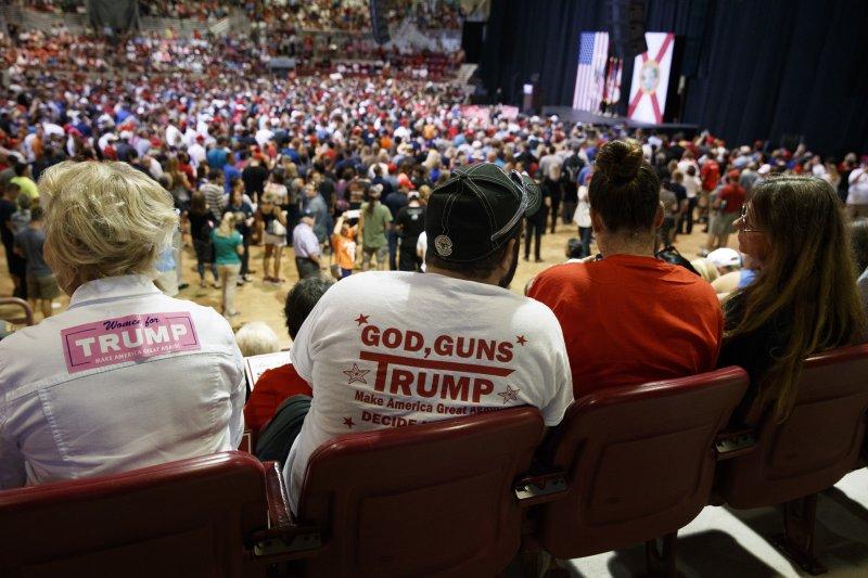 川普支持者穿著「上帝、槍枝、川普」標語的T恤。(美聯社)